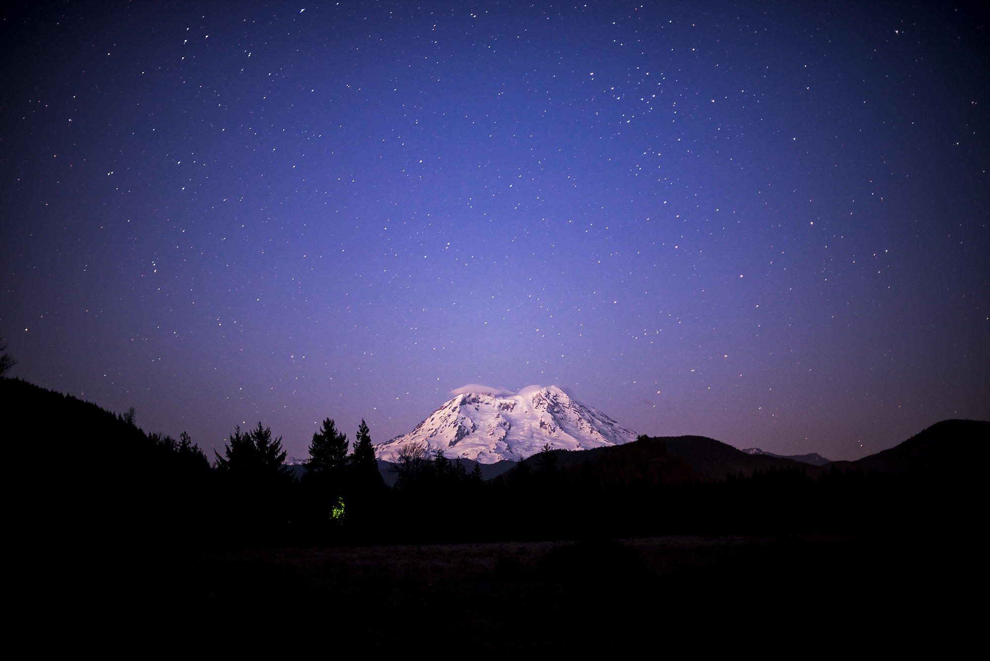 The stars sparkle in the twilight as Mount Rainier sits in the background on Monday, March 9, 2015 south of Elbe along State route 7.